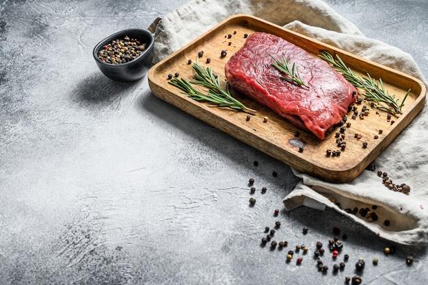 Bife de lombo cru em uma bandeja de madeira. carne bovina. fundo cinza. vista do topo. espaço para texto