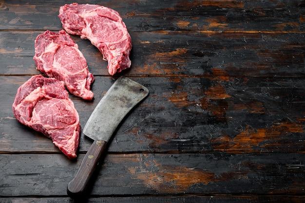Bife de lombo de carne bovina marmorizada ou conjunto de filé escocês e uma velha faca de cutelo de açougueiro, em uma velha mesa de madeira escura
