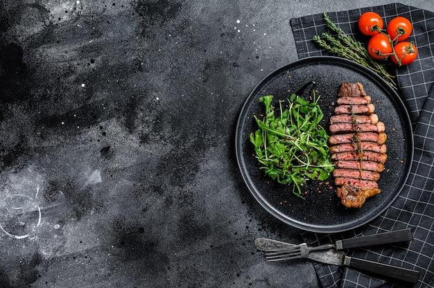 Bife de lombo grelhado na brasa, carne bovina marmorizada com rúcula