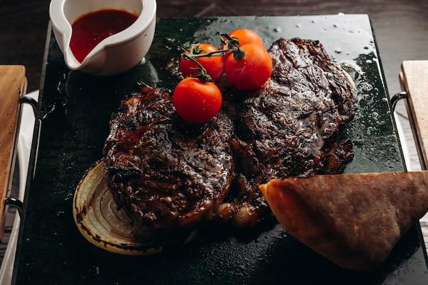 Bife de lombo grelhado servido no tabuleiro de pedra com tomate pão e molho