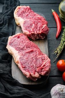 Bife de nova york, carne bovina crua, em fundo preto de madeira
