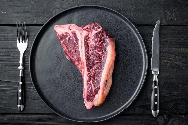 Bife de osso cru macio de corte nobre para um conjunto de churrasco, no prato, no fundo da mesa de madeira preta, vista de cima plana
