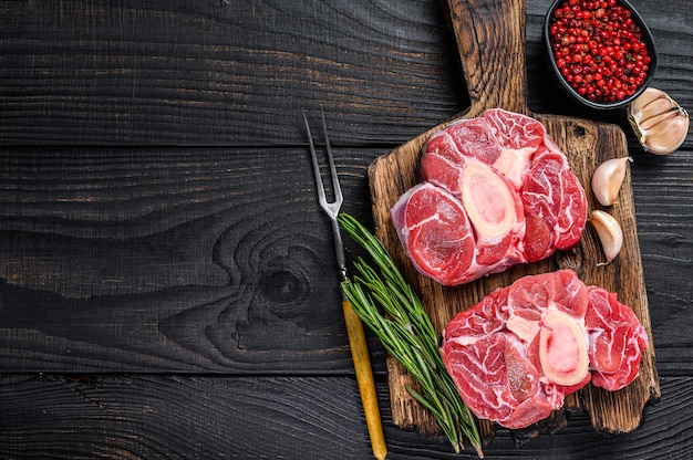 Bife de ossobuco de vitela com carne crua, confecção de ossobuco italiano. fundo de madeira preto. vista do topo. copie o espaço.