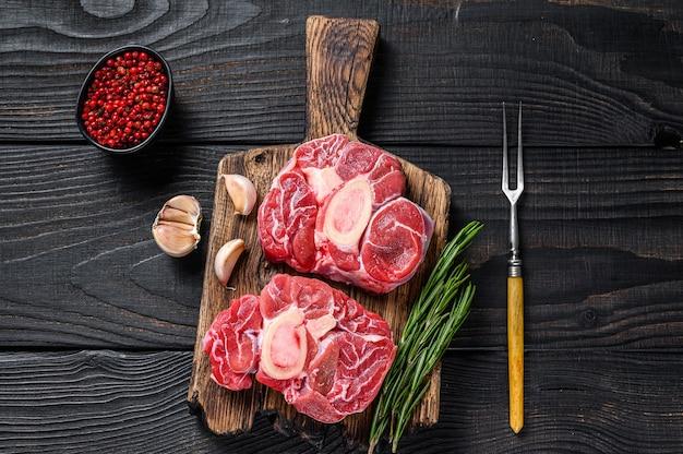 Bife de ossobuco de vitela com carne crua, confecção de ossobuco italiano. fundo de madeira preto. vista do topo.