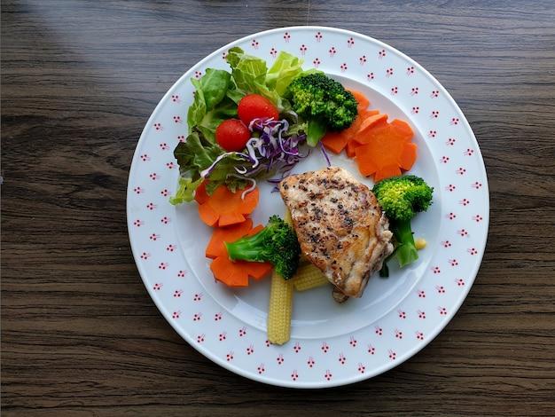 Bife de pargo com brócolis, cenoura, milho, tomate, alface repolho roxo em um prato branco