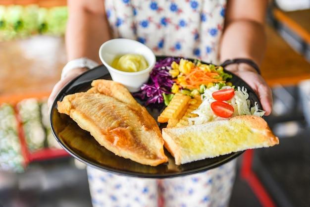 Bife de peixe com molho de creme de batata frita pão e legumes frescos no prato