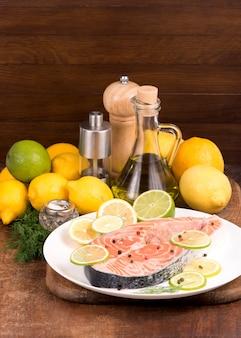 Bife de peixe vermelho e fatias de limão na mesa de madeira