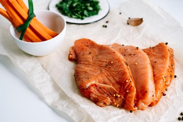 Bife de peru marinado com especiarias em um papel de cozinha com palitos de cenoura e ervas na mesa.