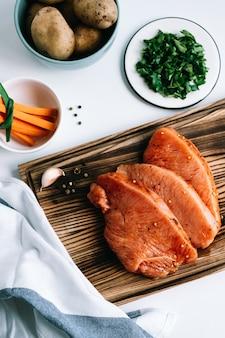 Bife de peru marinado com especiarias em uma placa de madeira com palitos de cenoura e ervas na mesa.