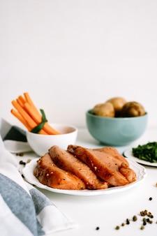 Bife de peru marinado com especiarias num prato branco com palitos de cenoura e batata na mesa.