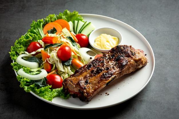 Bife de porco assado e legumes no prato.