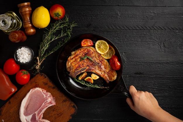 Bife de porco assado na superfície de madeira escura.