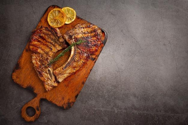 Bife de porco assado na superfície escura.