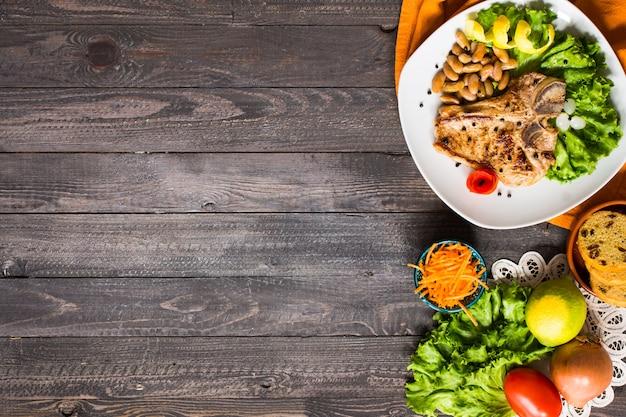 Bife de porco caseiro de cozinhar com especiarias folhas de alface na tábua de madeira e um prato,