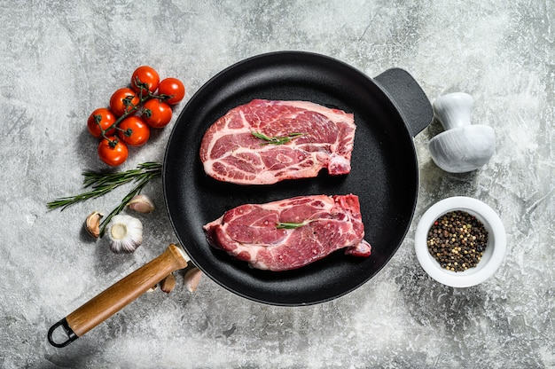Bife de porco cru em uma frigideira. carne de fazenda marmorizada. fundo cinza. vista do topo. espaço para texto.