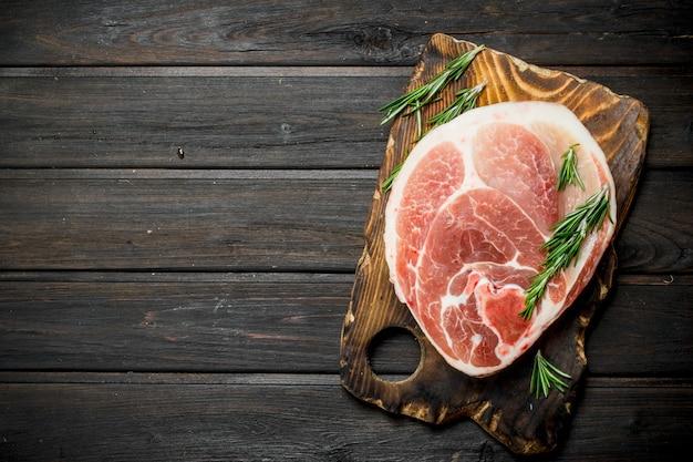 Bife de porco crua grande com alecrim na tábua. em uma madeira.