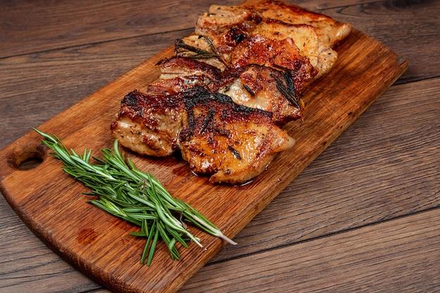 Bife de porco e raminho de alecrim na tábua de madeira.