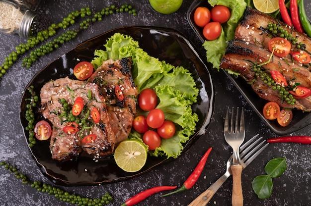 Bife de porco fatiado coberto com gergelim branco e sementes de pimenta fresca junto.