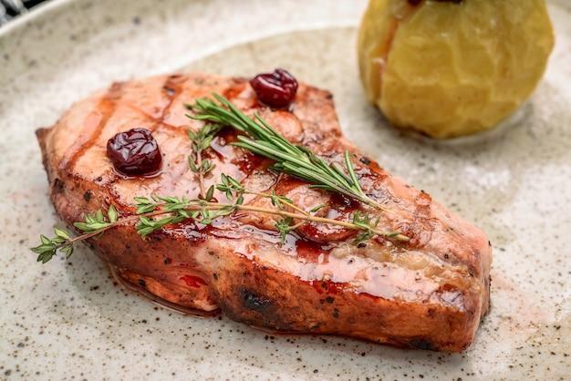 Bife de porco no osso com molho de gengibre e cereja com ingredientes em fundo de saco de carvão bagunçado.