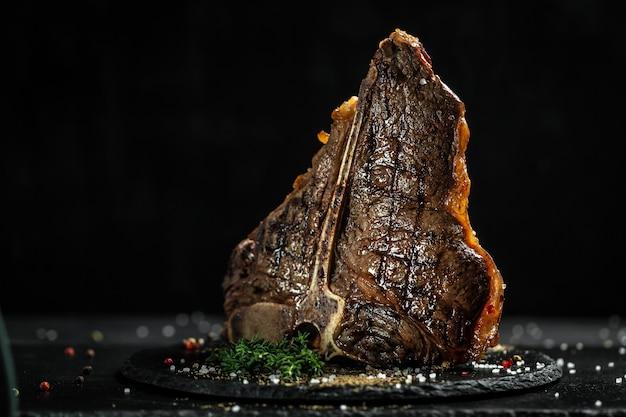 Bife de porterhouse de churrasco envelhecido. carne bife suculento bife bife com especiarias em uma mesa preta, banner, lugar de receita de menu de catering para texto.