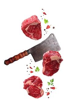 Bife de ribeye marmoreado cru e faca de açougueiros isolado
