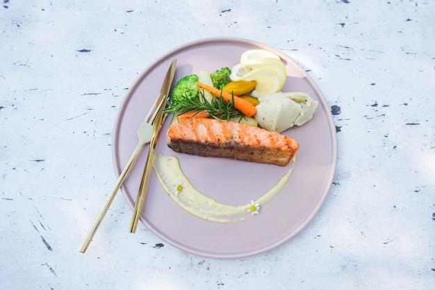 Bife de salmão com brócolis vegetais cenoura alecrim e limão no prato de frutos do mar - peixe bife de salmão assado ou grelhado na mesa de jantar comida ao ar livre