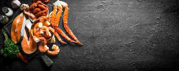 Bife de salmão cru com camarão cozido, caranguejo e lagostim em mesa preta rústica