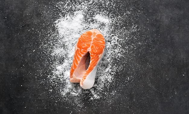 Bife de salmão cru e sal em um fundo preto de concreto.