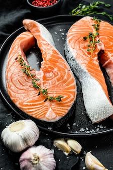 Bife de salmão cru em um prato com especiarias. peixe atlântico. fundo preto. vista do topo