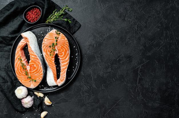 Bife de salmão cru em um prato com especiarias. peixe atlântico. vista do topo