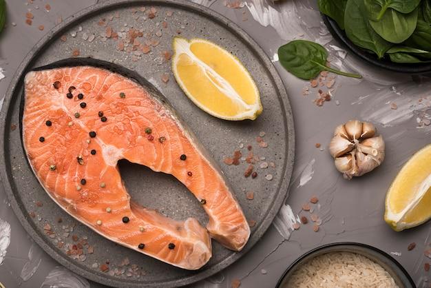 Bife de salmão cru liso leigos na bandeja com ingredientes