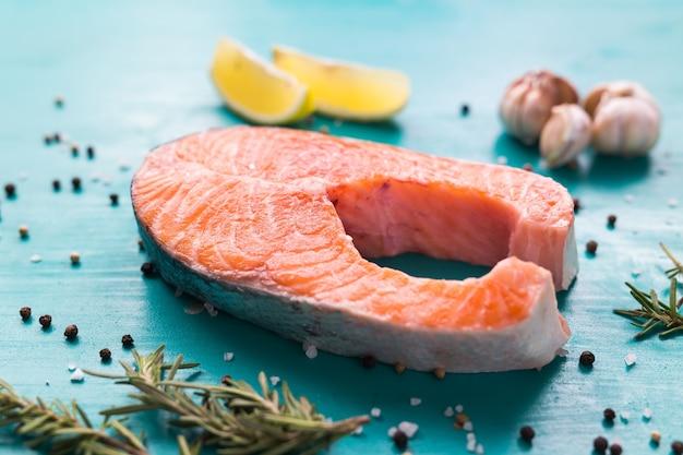 Bife de salmão cru na madeira na superfície azul