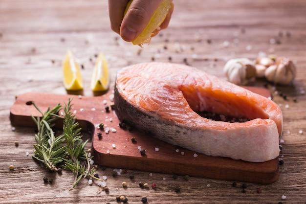 Bife de salmão cru na tábua de madeira