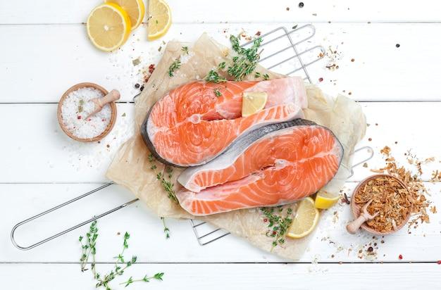 Bife de salmão cru na vista de topo de mesa de madeira branca