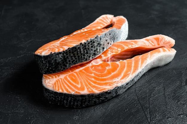 Bife de salmão cru. peixe atlântico. fundo preto. vista do topo