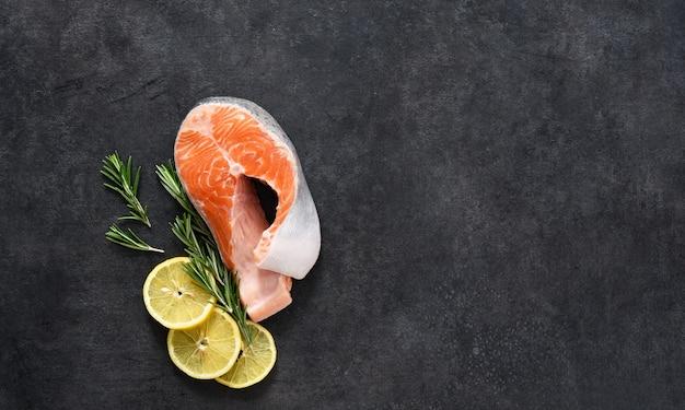 Bife de salmão cru, sal e alecrim em um fundo preto de concreto. ingredientes para cozinhar peixes.