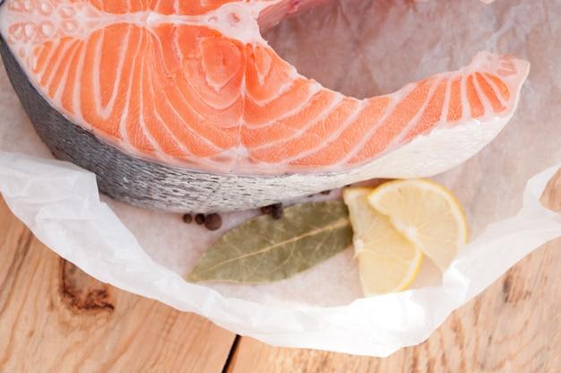 Bife de salmão cru vermelho peixe e especiarias na mesa de madeira. vista do topo