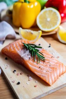 Bife de salmão fresco com ervas, limão e ingredientes para cozinhar na cozinha