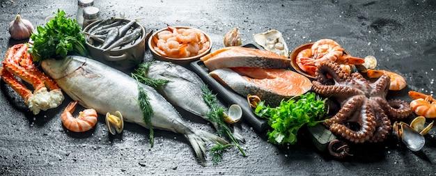 Bife de salmão fresco com variedade de frutos do mar e ervas. em preto rústico
