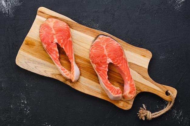 Bife de salmão fresco cru na tábua de madeira