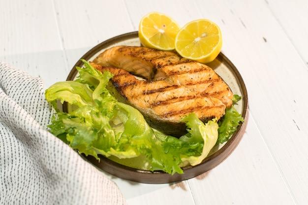 Bife de salmão fresco grelhado com folhas de alface em prato de madeira