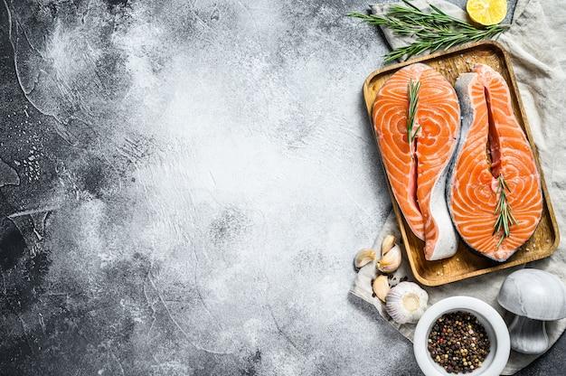 Bife de salmão fresco na bandeja de madeira com especiarias. peixe atlântico. vista do topo. copyspace fundo