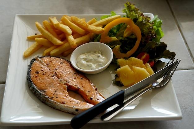 Bife de salmão grelhado com salada de estragão e batata frita