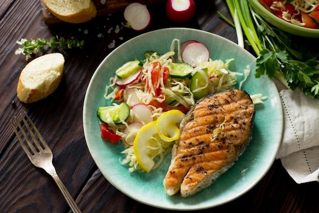Bife de salmão grelhado e salada de vegetais vegetariana de salada de alface rabanete comida saudável