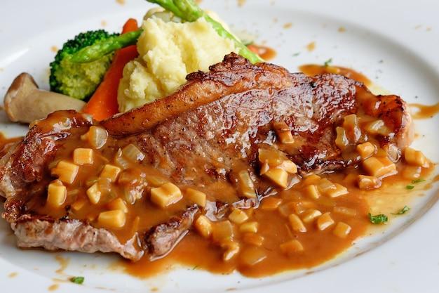 Bife de striploin de carne grelhada com purê de batata e legumes