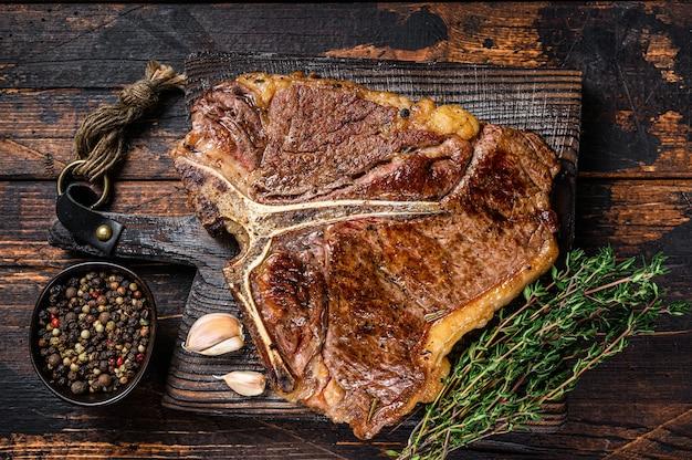 Bife de t-bone ou carne de vaca assada em uma tábua de madeira. fundo de madeira escuro. vista do topo.