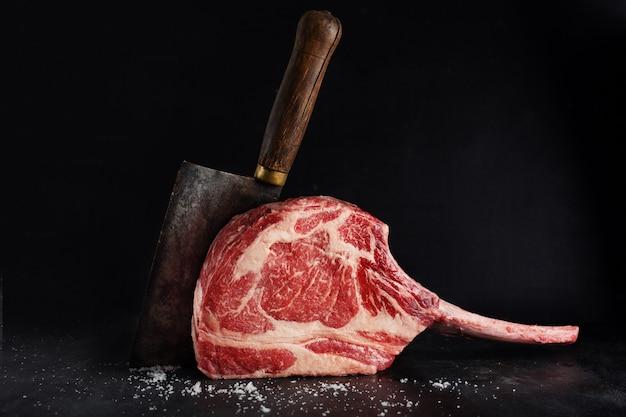Bife de tomahawk de carne fresca na prancha de madeira velha. fundo escuro. fechar-se