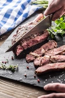 Bife de tomahawk recém grelhado na placa de ardósia com ervas de alecrim e salsa de pimenta. chef com faca corta suculento bife bovino