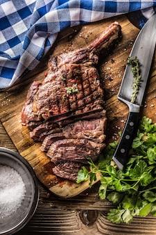 Bife de tomahawk recém grelhado na placa de ardósia com ervas de alecrim e salsa de pimenta. pedaços de bife suculento.