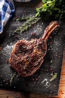 Bife de tomahawk recém grelhado na placa de ardósia com ervas de alecrim e salsa de pimenta.